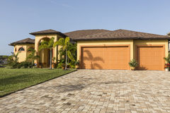Large pink and yellow tropical house with circular driveway. Stock Photos