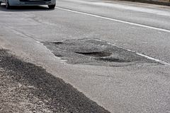 Large pit, potholes on the road. And car royalty free stock photo