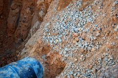 A large pit / ravine with a pipe, sand and stones. Repair stock images