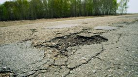 A large pit on the road. Cracked ruined asphalt pit roads, panning shot in sunny summer day.