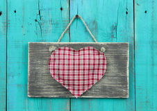 Large plaid heart on rustic sign hanging on vintage teal blue wood door. Red checkered heart on old sign hanging on antique greenwooden fence Royalty Free Stock Image