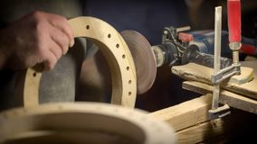 A large plan, hands of an artisan working on a wooden part.  Royalty Free Stock Image