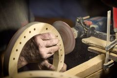 A large plan, hands of an artisan working on a wooden part.  Royalty Free Stock Photo