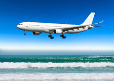 Large plane approaches the landing at the airport low over a tropical beach.  royalty free stock image