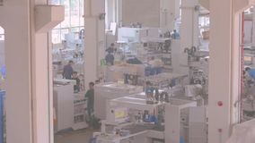 Spacious hall of a large modern enterprise with a large number of working people. Large plant for the production of machine tools, the overall plan of the plant stock footage