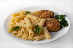 A large plate with pasta and two cutlets, decorated with parsley on a white tablecloth. royalty free stock image