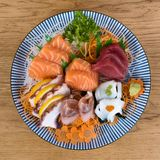 Large plate of sashimi, raw and fresh sliced fish served with vegetables. Large plate of sashimi, raw and fresh sliced fish, squid and octopus served with royalty free stock photo