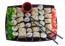 A large plate with a wide selection of different sushi. A large plate with many different kinds of sushi rolls with seaweed salad, pickled ginger, small bowl of Stock Photos
