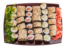 Large plate with a wide selection of sushi, seaweed and ginger. A large plate with a wide selection of home made sushi with a side of seaweed salad and pickled Royalty Free Stock Image