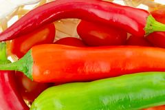 Large pods of red hot pepper a piece of a long green vegetable in a tomato basket close-up stock images