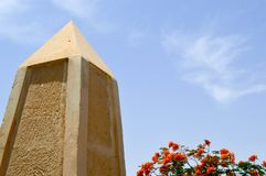 A large pointed obelisk made of yellow stone in Egypt against a blue sky and red flowers stock photo