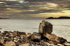 Large pointed stone among the rocky formations by the sea stock photos