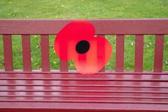A large poppy has been placed on the bench in commemoration for the ending of the Great War stock image