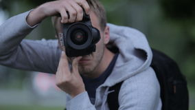 A Large Portrait Of A Man With A Professional SLR Camera In Hand stock video footage