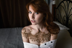 A large portrait of a redhead girl sitting on a bed in a white shirt flung down from her shoulders and mehendi on her chest. Horizontal photo Stock Photos