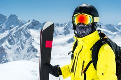 A large portrait of a skier in a protective helmet and glasses - a mask and a scarf next to the skis against the snow. Capped mountains of the Caucasus. Skiing Stock Photography