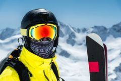 A large portrait of a skier in a protective helmet and glasses - a mask and a scarf next to the skis against the snow. Capped mountains of the Caucasus. Skiing Royalty Free Stock Photography