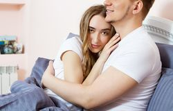 Large portrait : Young lovely couple on bed, morning bedroom. Happy loving couple in the bedroom in morning Copy space . Family stock photography