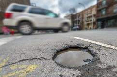 Large pothole in Montreal. Large rounded pothole on Laurier street in Montreal, Canada 2018 stock photos