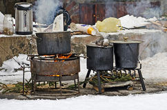 Large pots for cooking over an open fire outdoors in the winter Stock Photography