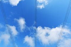 Large power line wires against the blue sky with clouds.  Royalty Free Stock Images