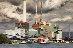 Large power plant and smoky looking sky. Large power plant blowing out steam and appearing to pollute the sky royalty free stock photo