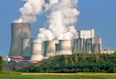 Large power plant on a sunny day. Power plant with huge cooling towers, in contrast to its nice surrounding area stock image