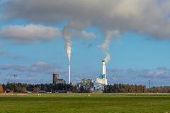 Large power plant in Sweden polluting the environment and atmosphere. Large power plant in Sweden with large smoke stacks polluting the atmosphere. Autumn view stock photography