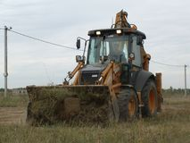 Large powerful tractor removes the earth works on construction site royalty free stock images