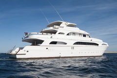 Large private motor yacht out at sea. A large private motor yacht under way sailing out on tropical sea Stock Photography