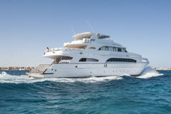 Large private motor yacht out at sea. A large private motor yacht under way sailing out on tropical sea Stock Image