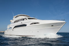Large private motor yacht out at sea. A large private motor yacht under way sailing out on tropical sea Royalty Free Stock Photo