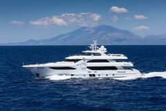 Large private motor yacht at sea. With a mountain on the background royalty free stock photos