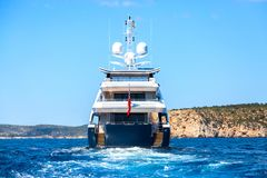 A large private motor yacht underway out at sea, back view stock image