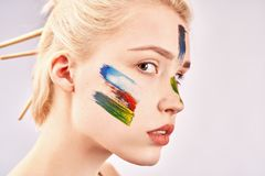 Large profile portrait of beautiful woman, has creative hairstyle, ponytail stuck brushes for drawing, has short Bob haircut. On face of girl painted royalty free stock image