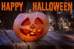 A large pumpkin with a smiling face and burning candles inside. Symbol Halloween in the twilight forest. Above is the stock image