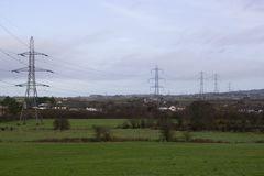 Large pylons and cables carrying electricity generated at Ballylumford Power Stationy into the grid. Large pylons and cables carrying electricity generated at Royalty Free Stock Photography