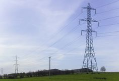 Large pylons and cables carrying electricity generated at Ballylumford Power Stationy into the grid. Large pylons and cables carrying electricity generated at Royalty Free Stock Images