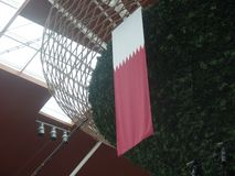 Qatari flag hanging from a display. Large Qatari national maroon and white flag hanging from a display stock images