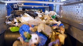 A large quantity of trash moving on a waste conveyor. Conveyor transporting a large amount of trash at waste processing plant stock video