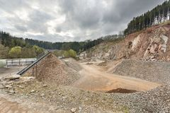 Quarry in the Ardennes, Belgium. A large quarry in the Ardennes, Belgium with dark clouds, a rest of forest on the hill top Royalty Free Stock Photography