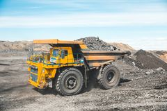 Large quarry dump truck. Loading the rock in dumper. Loading coal into body truck. Production useful minerals. Mining royalty free stock images