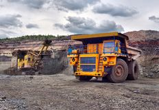 Large quarry dump truck. Loading the rock in the dumper. Loading Royalty Free Stock Image