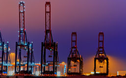 Large quay cranes at night. Container terminal scene in the Port of Rotterdam against night sky Stock Images