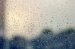 Large raindrops on clear glass on a rainy cloudy day. Large rain drops on transparent glass in a rainy grey gloomy day stock photos