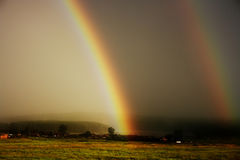 Large rainbow. During thunderstorm over farmers field Stock Photos