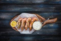 Large red Argentine shrimp or langoustine with white sauce and half a lemon on a wooden board. Top view.  Stock Photo