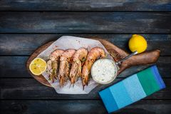 Large red Argentine shrimp or langoustine with white sauce and lemon. Served with napkins on a wooden board. Top view Stock Images