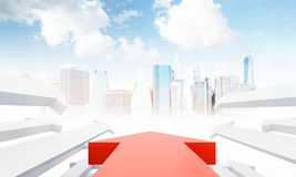 Large red arrow pointing to big city. Large red arrow in the center and smaller white arrows by its sides pointing to modern city with skyscrapers. Concept of Stock Photography
