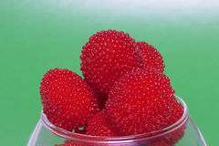 Large red berries are similar to raspberries in a glass vase. Royalty Free Stock Images